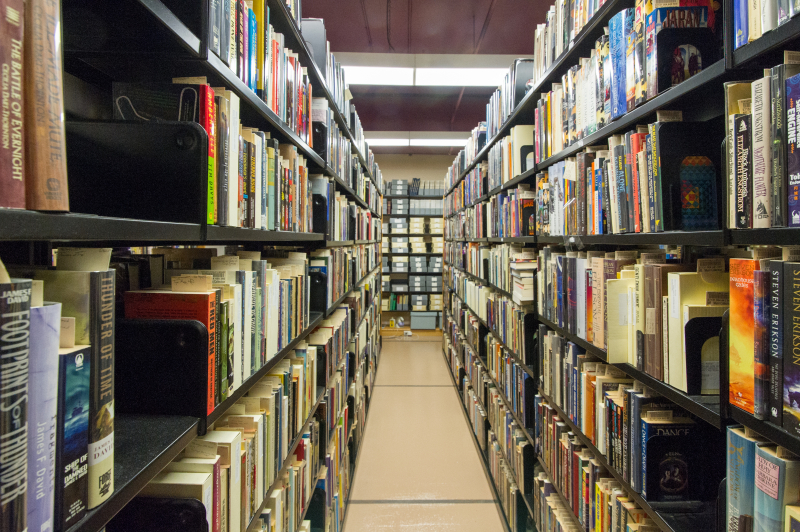 The reference stacks of the Merril Collection are shown. Books fill the shelves on both sides of an aisle. They are marked with archival flags.