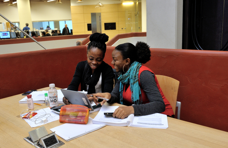 Young women working on tablet at library