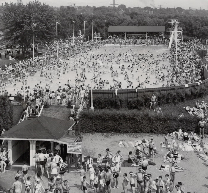 Zoomed out view of crowded outdoor pool and entry point