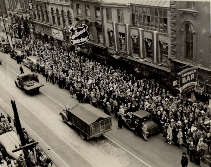Vintage image of packed sidewalks in urban area with a few military style vehicles on the empty road