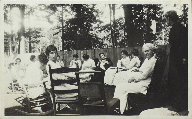 Women sitting in circle outdoors on rocking chairs knitting