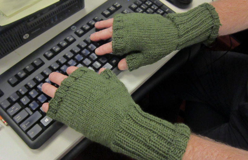 Hands at keyboard with knitted gloved with top half of fingers and thumb exposed