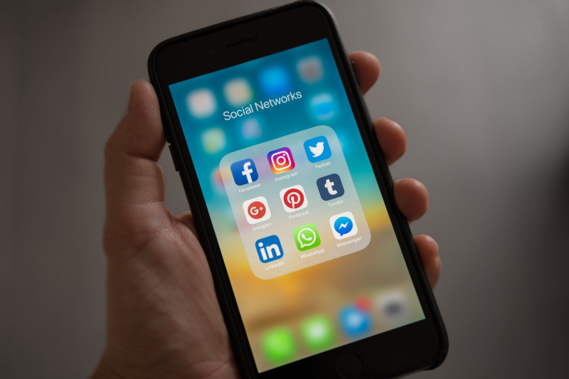 Person holding cell phone showing social networks icons