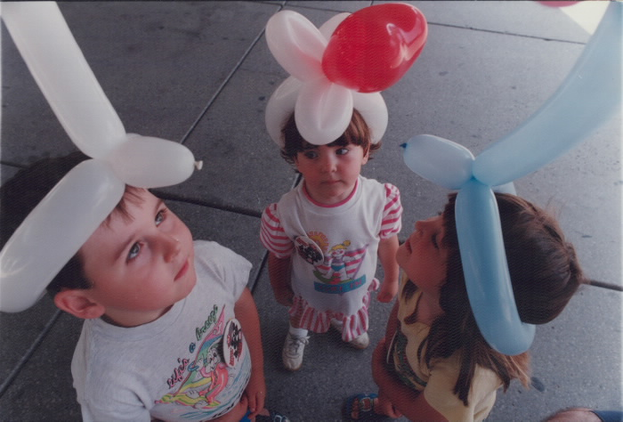 Three children wearing hats made out of balloons.