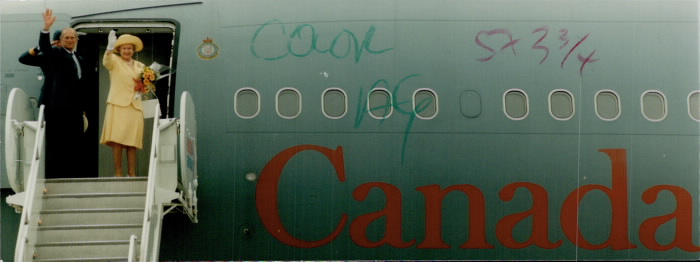 Prince Philip and Queen Elizabeth waving in front of plane entrance with Canada written on Plane and some scribblings on plane