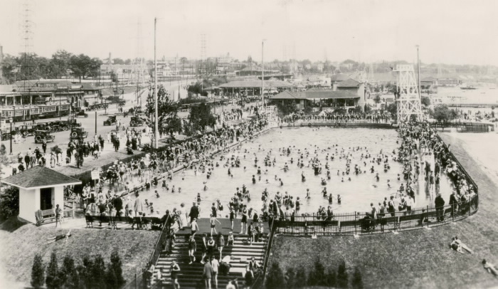 Large outdoor pool with lots of swimmers and people on the sides of it