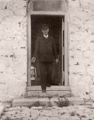 Man in uniform holding lantern coming out of door