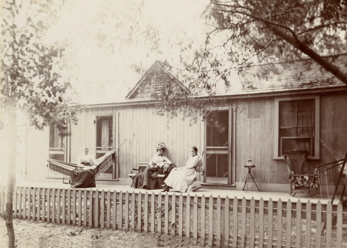 Vintage photo of three women sitting outside a cottage