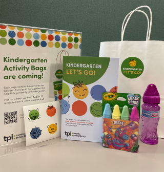 A Kindergarten Let's Go activity booklet, displayed with stickers, a pack of 4 sidewalk chalk, a bottle of bubble solution. A white paper bag with a round green sticker. A sign with text: Kindergarten Activity Bags are coming!