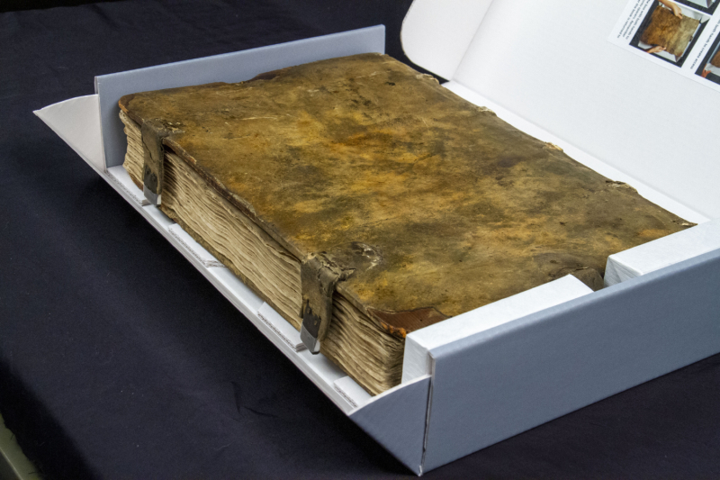 Old book with blank cover and clasps inside white book with lid open