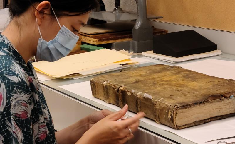 Conservator in mask handling old book in lab