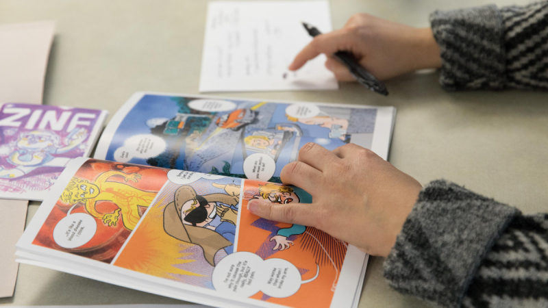 Left hand holding open a graphic novel on a table, while the right hand makes notes with a pen on a piece of paper