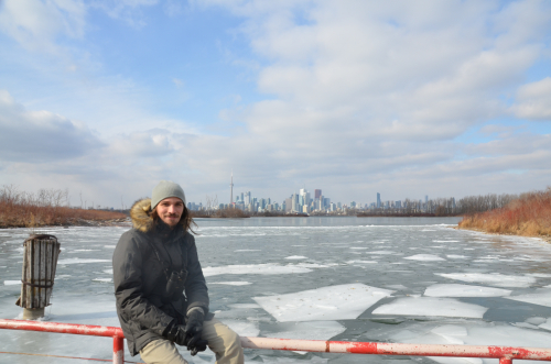 Andrés in front of a frozen lake and the Toronto skyline in the winter