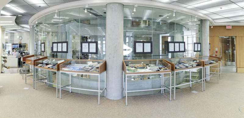 Eight glass display cases are shown in the Merril Reading Room displaying books from the collection.