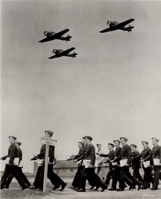 A group of men marching with three airplanes flying overhead