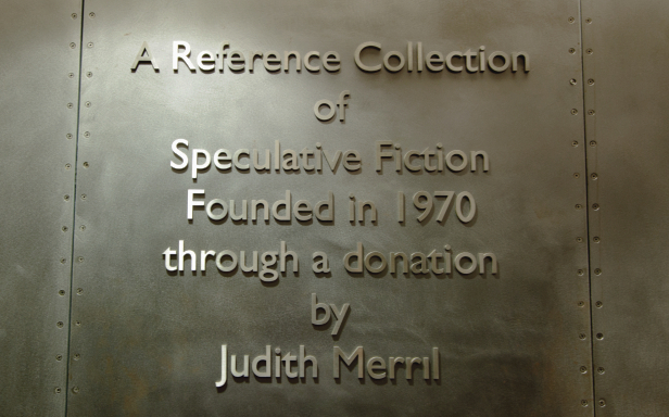 "Raised letters appear in a wall of sheet metal from the front of the Merril reading room. Text reads ""A Reference Collection of Speculative Fiction Founded in 1970 through a donation by Judith Merril"""