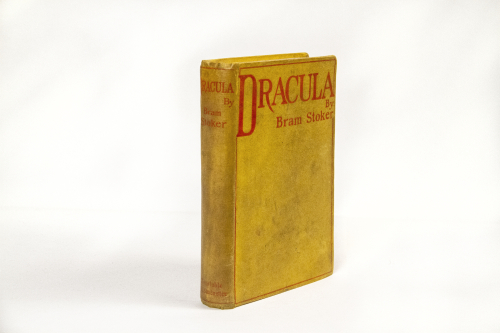 """A bright yellow hardcover of a book with a thin red border. The title at top reads """"Dracula"""""""