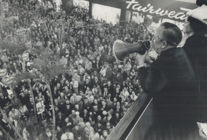Man on balcony speaking in megaphone to a packed audience below