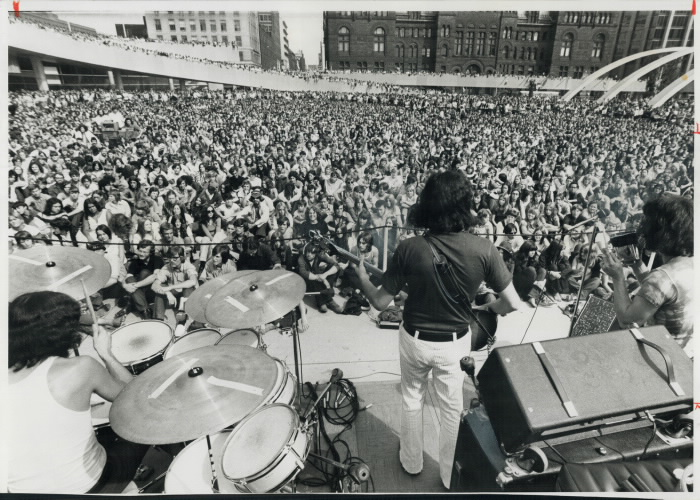 View of large crowd from behind a band on stage