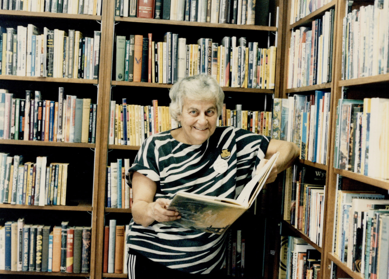 A woman with grey hair and a stripped shirt poses with an open book in front of bookshelves