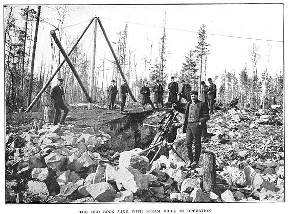 Apparatus on rocks with 10 men standing by looking at camera and subtitle The Red Rock Mine with Steam Drill in Operation