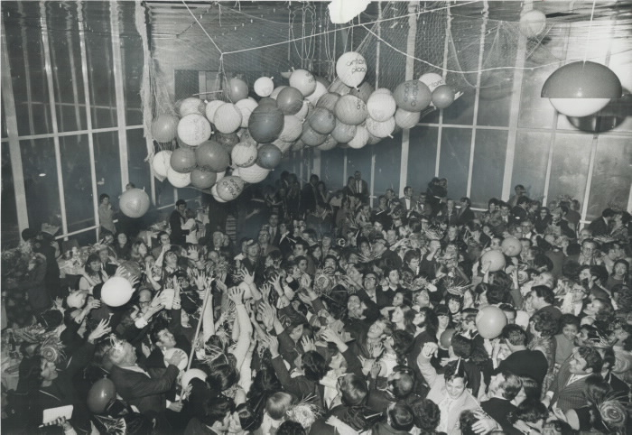 Packed party goers celebratin an indoor balloon dropjpg