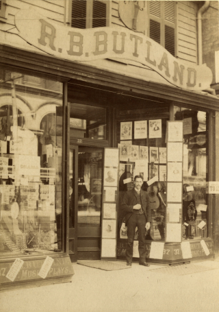 A man with a moustach stands outside a storefront. The sign for the store appears beneath a large violin. Instruments and sheet music can be seen in the window.