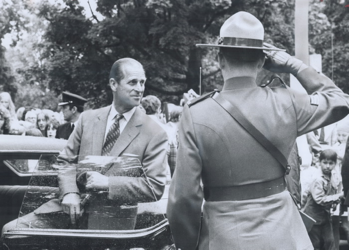 Prince Philip entering car with officer saluting him