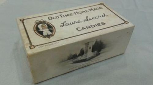 Photo of box of candies with Laura Secord image and text reading Old Time Home Made Laura Secord Candies and image of monument