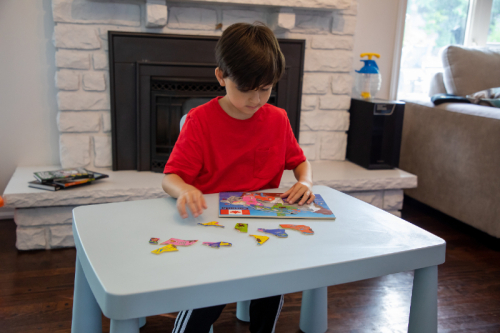 Kid sitting at a table and working on a jigsaw puzzle. There is a fireplace and partially seen sofa in the background.