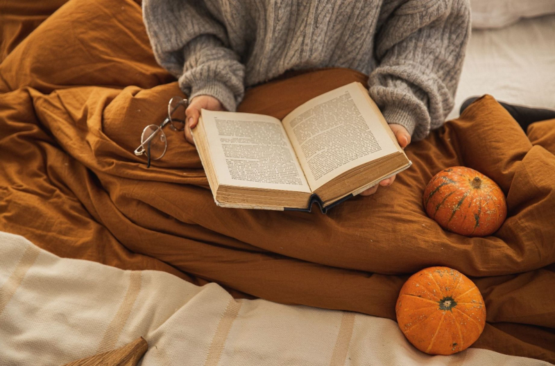 A person reads in a bed with fall-coloured sheets and a couple of pumpkins.