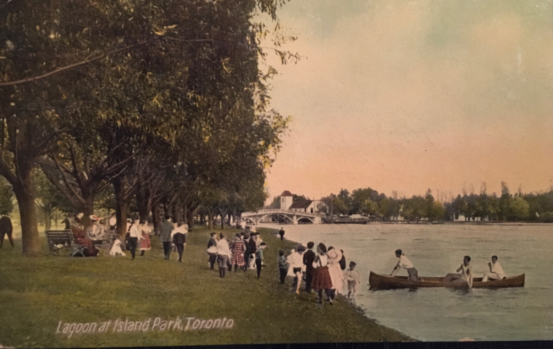 Vintage postcard of children and others by the water and a canoe approach and the words Lagoon at Island Park Toronto