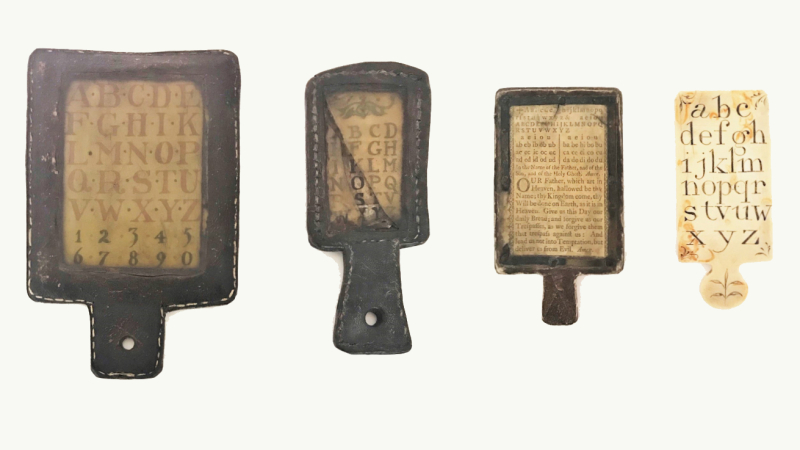 Four hornbook specimens, three of the hornbooks are made of leather and one hornbook is made of ivory and letters of alphabet visible